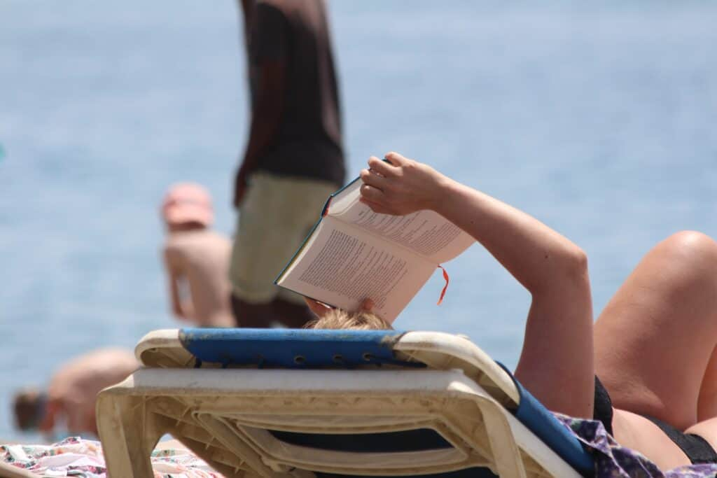 White person in bikini on beach chair reading a book they are holding up.